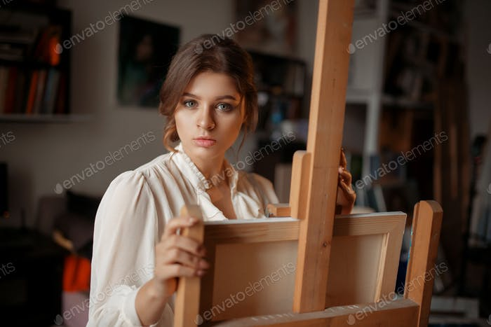Thoughtful female artist at the easel in studio