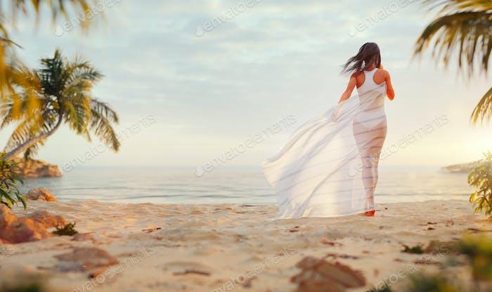 Junge glückliche sorglose Frau genießen schönen Sonnenuntergang am tropischen Strand.