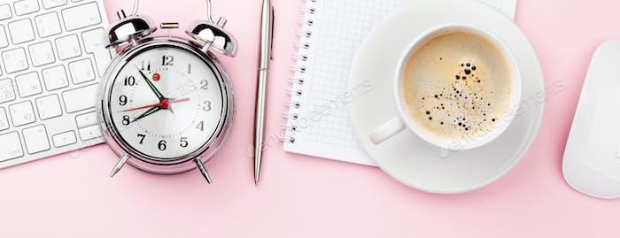 Rosa Arbeitsplatz mit Computer, Zubehör, Kaffee und Alarm