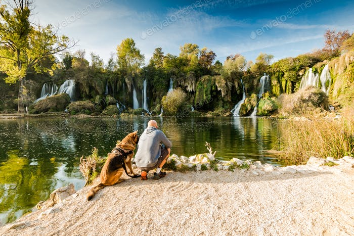 Active man sitting with dog at Kravica waterfall,Bosnia