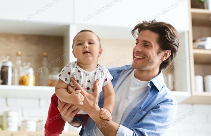 Young father raising his baby son like on plane at kitchen
