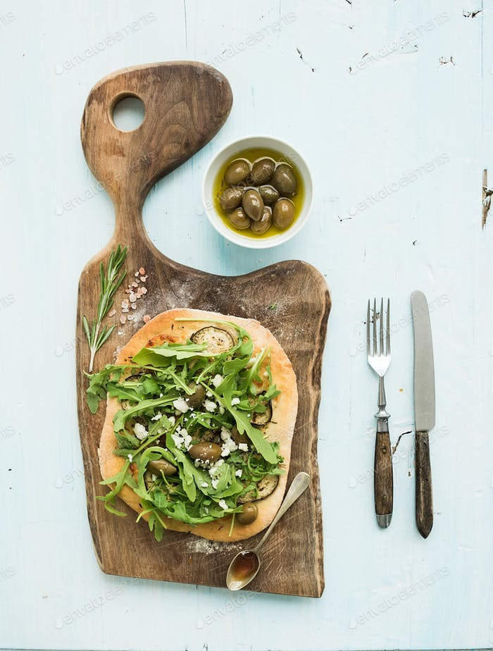 Rustic homemade pizza with eggpant, cheese, olives and arugula