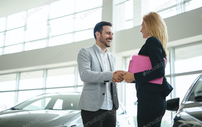Professional salesperson during work with customer at car dealership