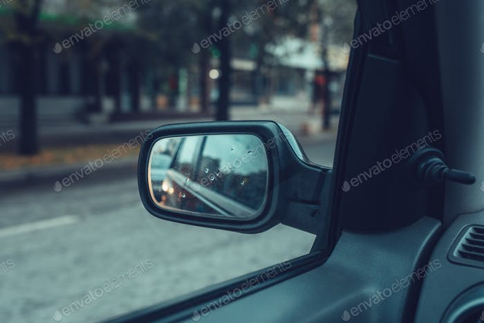 Reflection of city traffic in car side mirror