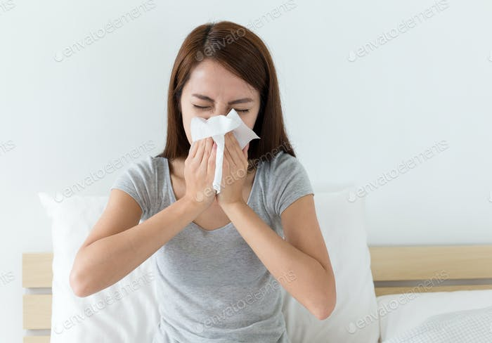 Woman sneeze on bed