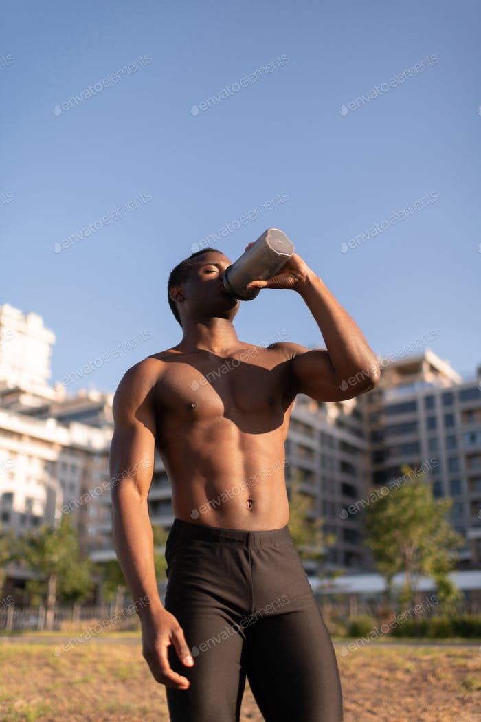 Black athletic male enjoying water after exercising