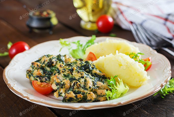 Baked steak chopped chicken fillet with spinach and a side dish of mashed potatoes.