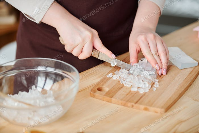 Hands of young craftswoman with knife cutting transparent soap mass on board