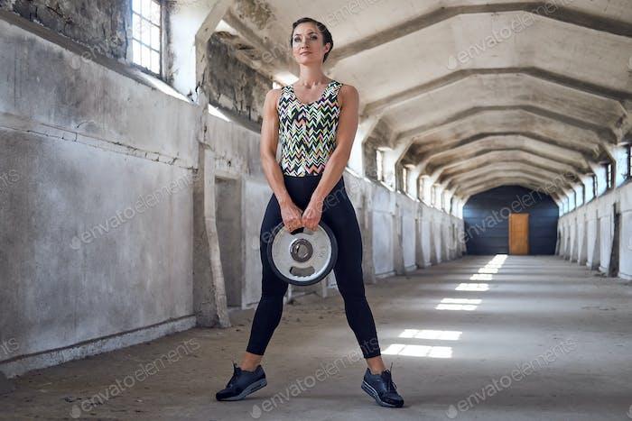 Ganzkörperporträt der sportlichen Frau, die Kniebeugen macht.