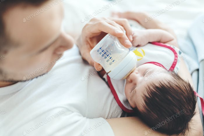 Young white father feeding baby with bottle