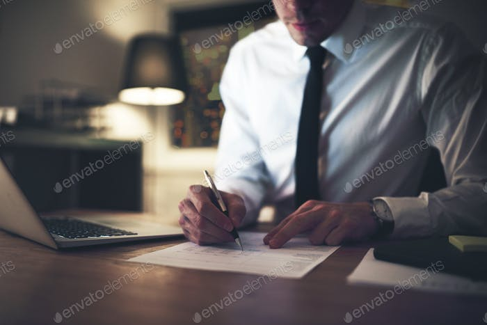 Serious businessman signing contract at office