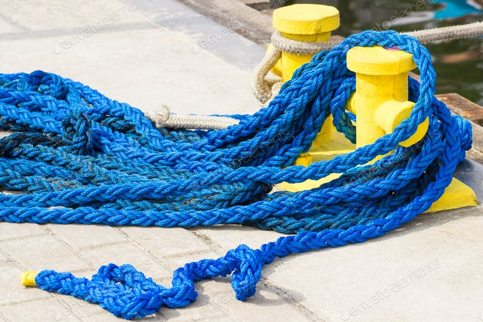 Blue rope and mooring bollard, detail of seaport, yachting concept