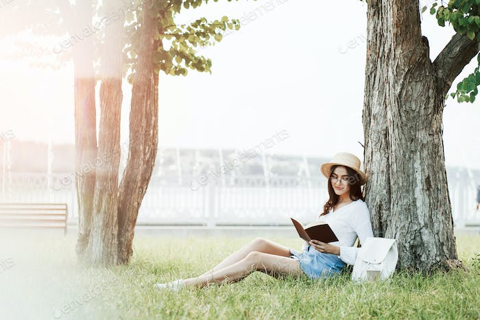 Illumination effect. Young woman have weekend and sits in the park at daytime