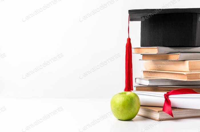 Academic hat on pile of books with diploma and apple isolated on white