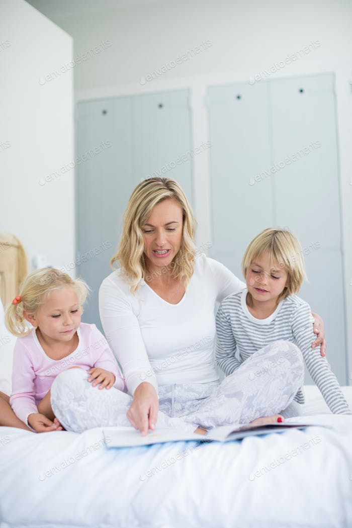 Kids and mother reading story book in bedroom