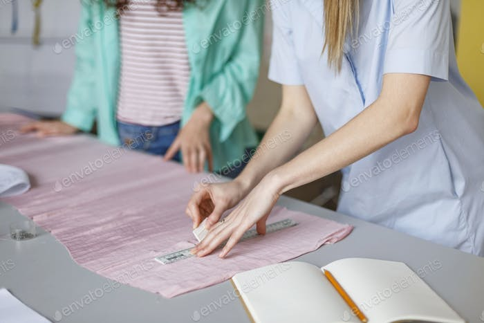 Close up fashion designers drawing with soap on pink textile in