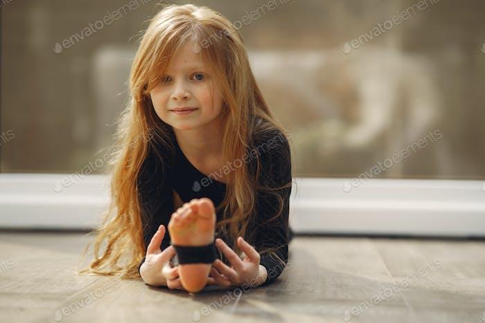 Little girl in a balck sportswear is engaged in gymnastics