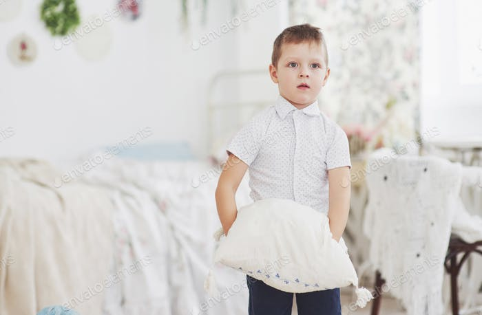 Little boy in white shirt with pillow