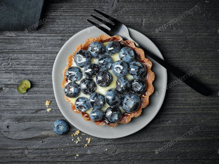 blueberry tart on dark wooden table