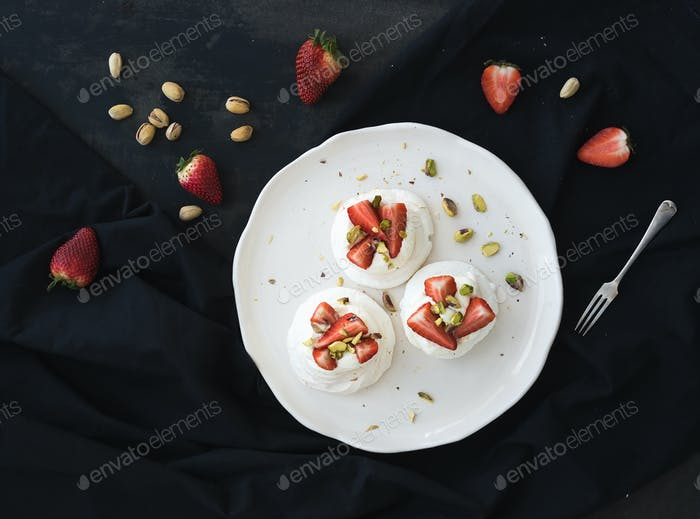 Small strawberry and pistachio pavlova meringue cakes with mascarpone cream