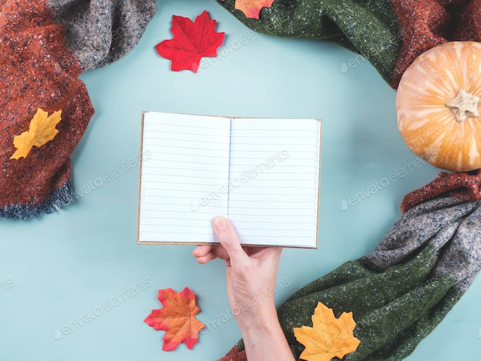 Empty notebook in female hand in scarf frame