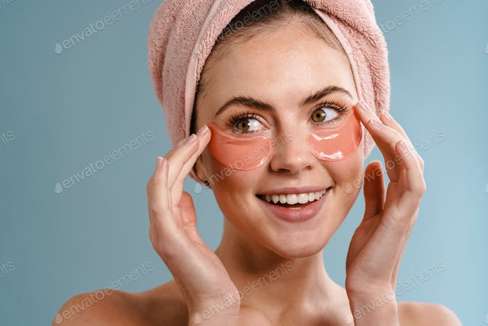 Smiling shirtless girl in towel posing with eye patches