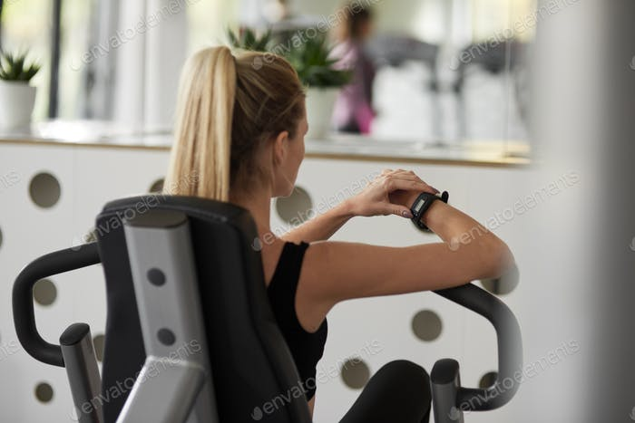 Rear view of female athlete using technology at the gym