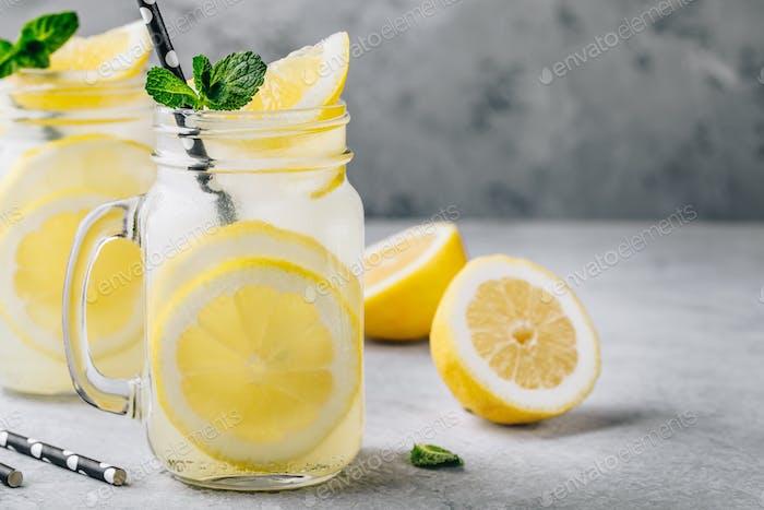 Hausgemachtes erfrischendes Sommerlimonade Getränk mit Zitronenscheiben und Eis in Mauergläsern