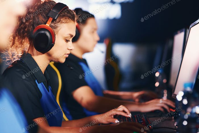 Side view of a focused mixed race girl, female cybersport gamer
