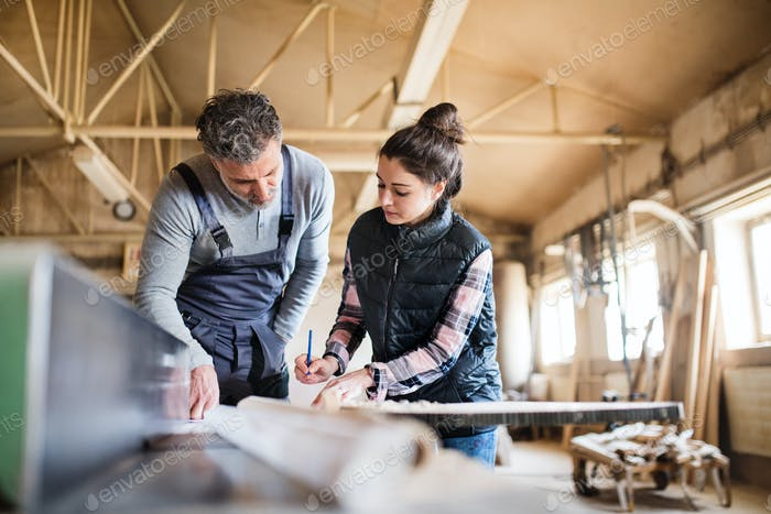 Man and woman workers working in the carpentry workshop.