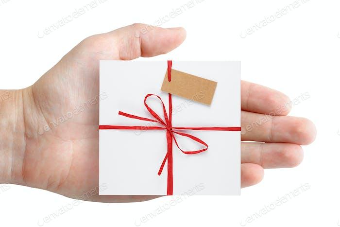 Geschenkbox mit Anhänger in Hand isoliert auf weißem Hintergrund