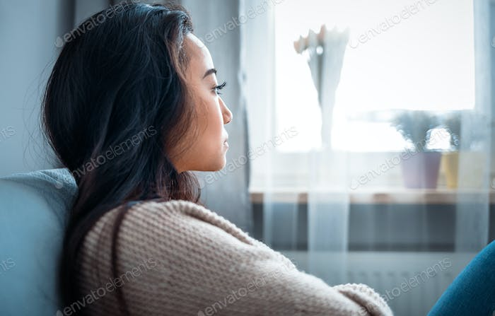 Depressed asian girl sitting on sofa at home and thinking