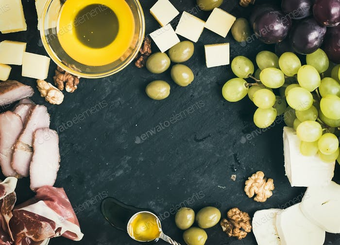 Wine appetizer set: cheese and meat selection with grapes, honey