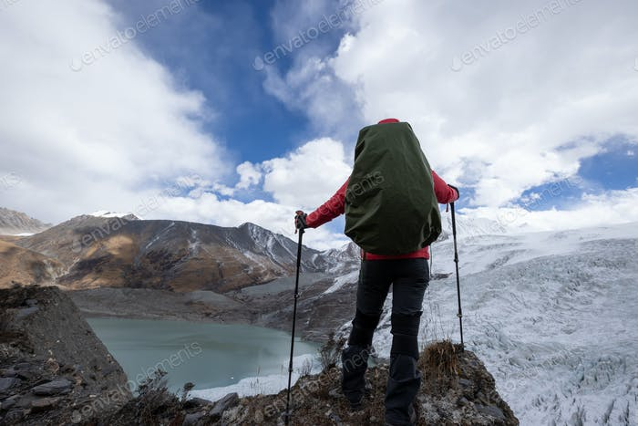 Successful woman backpacker hiking in winter mountains