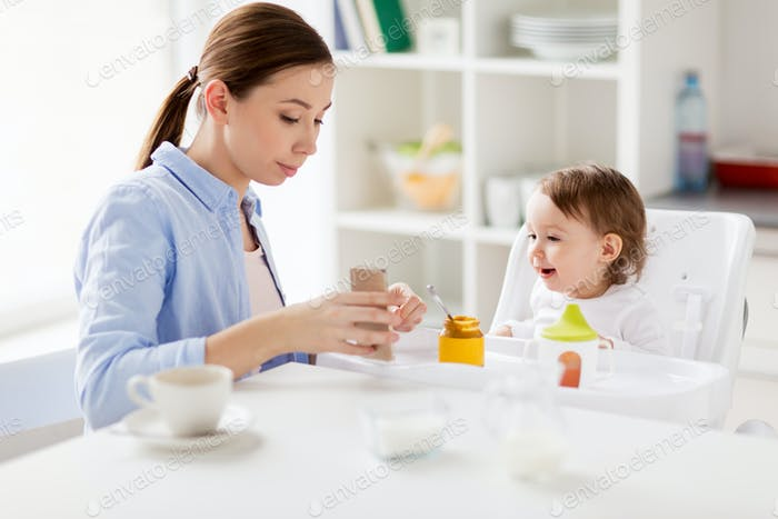 mother with smartphone and baby eating at home
