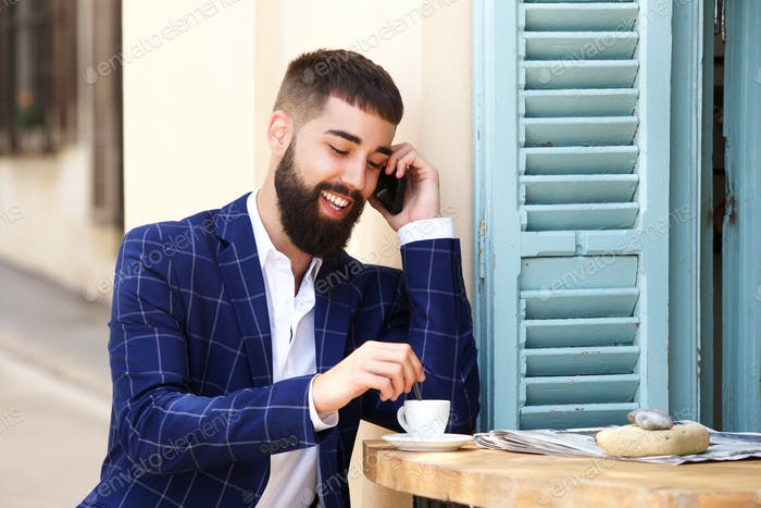 Cheerful businessman sitting at cafe with coffee talking on cellphone