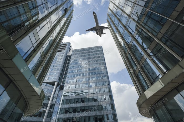 airliner flew above the modern glass building