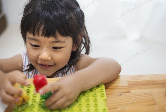 Familie zu Hause. Ein Mädchen, das mit zwei Puppen spielt.