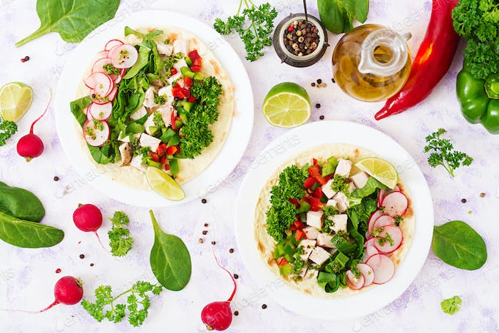 Healthy mexican corn tacos with boiled chicken breast, spinach, radish and paprika