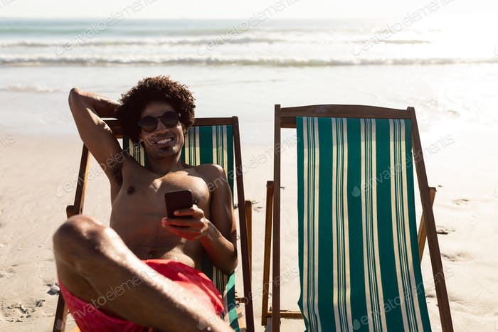 Happy African-american man using mobile phone while relaxing in a beach chair