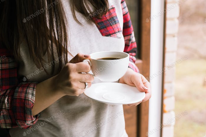 hands holding hot cup of coffee in morning