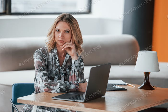 Analyzing your behavior. Businesswoman with curly blonde hair sitting in room against window