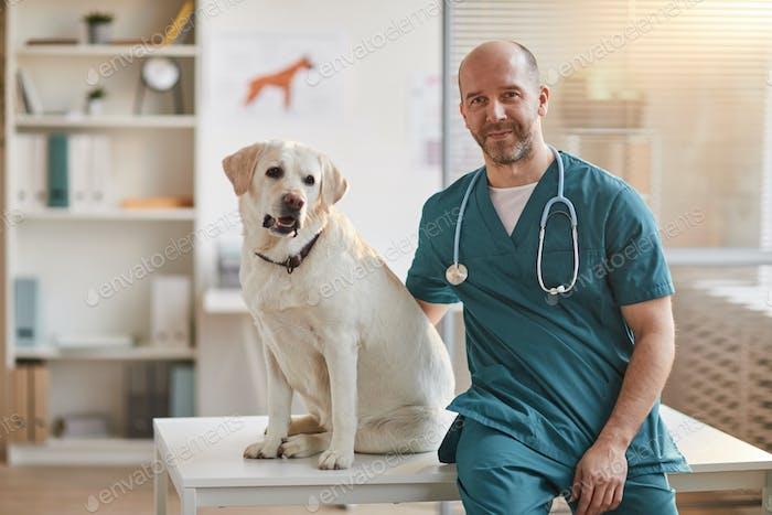Veterinario masculino posando con perro en la clínica veterinaria