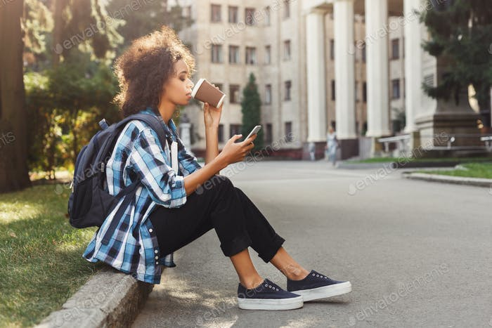 Student girl with backpack and mobile at university building background