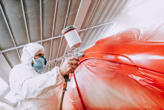 automotive industry mechanic engineer worker using spray gun and painting a red car