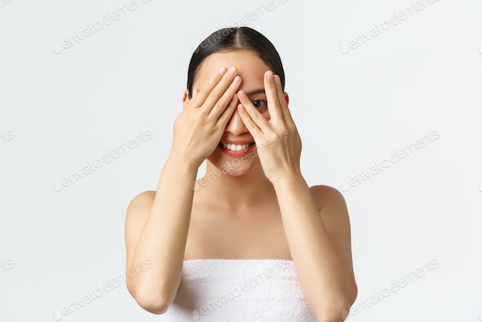 Beauty, cosmetology and spa salon concept. Silly beautiful asian girl in bath towel peeking through