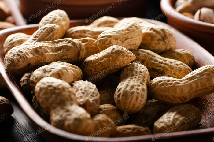 Peanuts in clay bowl on kitchen wooden table food background