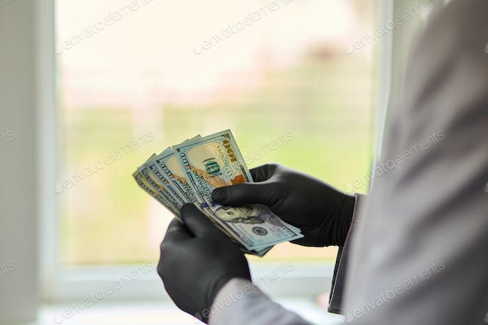 Man holding money dollars in hand in black medical gloves.