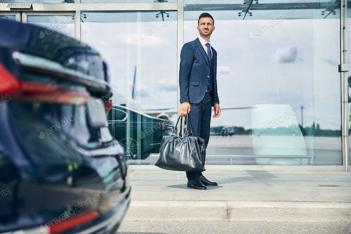 Elegant businessman waiting for a shuttle bus near the airport