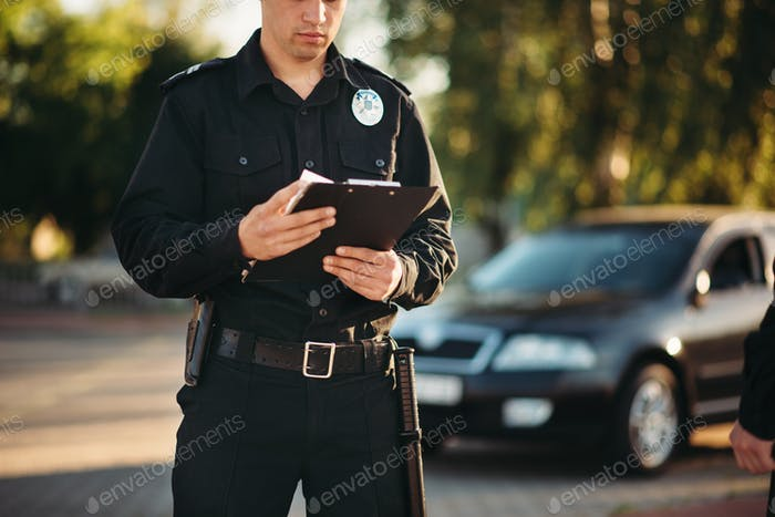 Cop with notebook in hands check the car